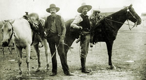 Two armed men in 1800s Ranger garb complete with hats standing next to their horses.