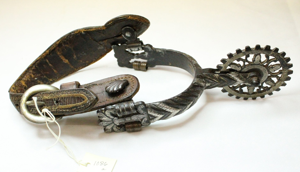 A highly decorative silver boot spur with a dark brown leather strap.