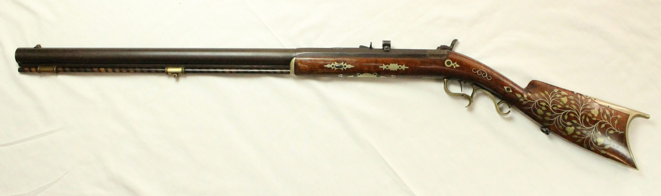 A percussion rifle with gold decorations and leaf and flower inlaid decorations along the butt of the firearm.
