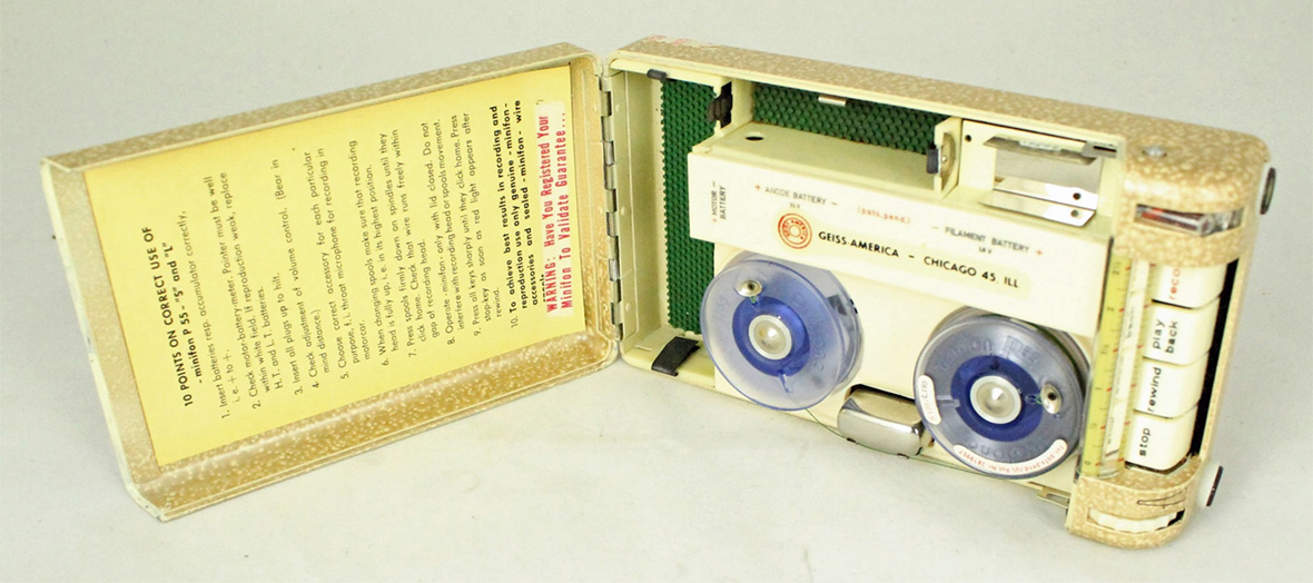 A tan recorder opened so you can see the two circles were the tape records along with instructions taped inside the lid.