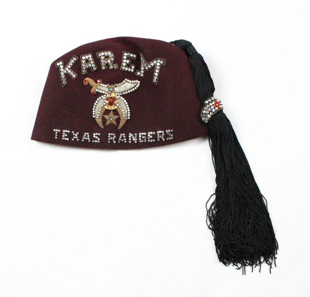 maroon hat with black tassle and embroidery